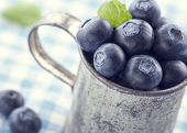 stock photo of hazy  - Closeup of fresh blueberries in an old metal cup with green leaves on a blue tablecloth with vintage hazy editing - JPG