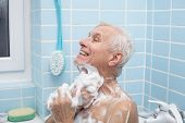 picture of bubble-bath  - Senior man washing his body with soap in bath - JPG