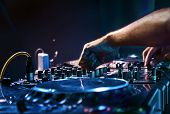 foto of disc jockey  - Dj mixes the track in the nightclub at party - JPG