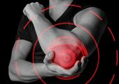 stock photo of elbow  - Man holds his the elbow joint acute pain in the elbow black and white image pain area of red color - JPG