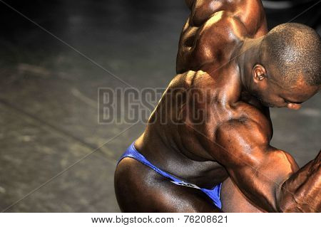 Male Bodybuilding Contestant Doing A Back Double Biceps Pose