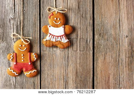 Christmas homemade gingerbread couple cookies over wooden background
