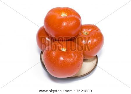 Four Tomatoes On A Plate On The White Background