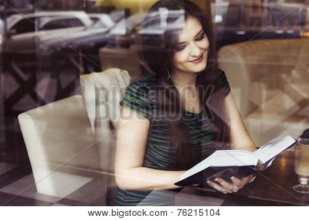 Brunette woman sitting at the cafe reading book studing and drinking coffee
