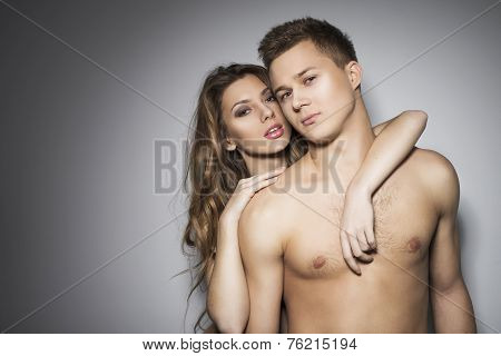 Woman and a man holding each other in sexy pose with lust in their eyes. Copy Space