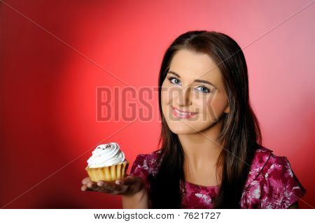 Young Beautiful Girl Eating Small Sweet Cake. Red Background. Copy-space