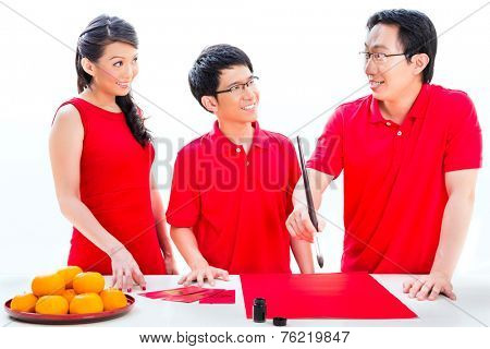 Friends family celebrate Chinese new year with traditional calligraphy, wearing red shirts