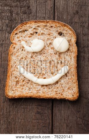 Winking smiley made from mayonnaise on slice of bread
