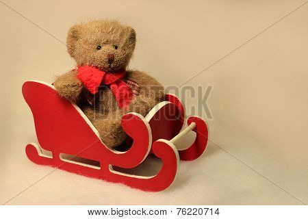 Teddy Sitting in a Red Sled