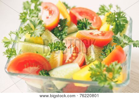 Fresh vegetables with greens in a transparent bowl on a light background