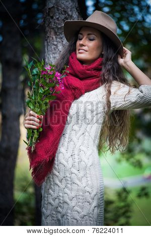 smiling young woman wearing hat,  red wool scarf and wool dress hold flowers in hand enjoy in autumn  day outdoor shot in forest