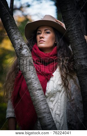 beautiful young woman wearing hat,  red wool scarf and wool dress lean on tree enjoy in autumn  day outdoor shot in forest