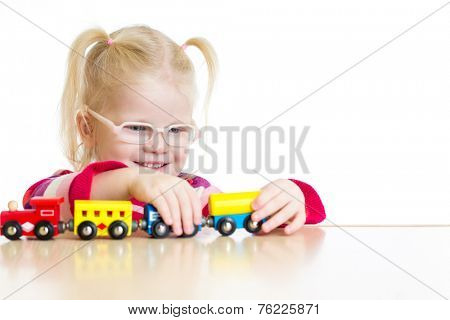 Child in eyeglasses playing toy train isolated  on white