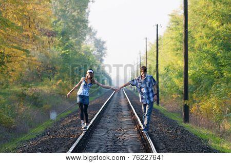Teen Girl And Boy Walking On Rails
