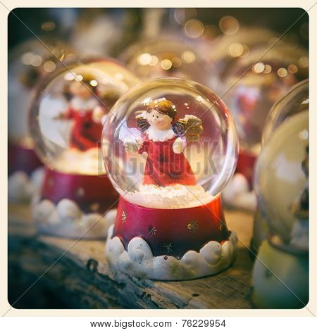 A festive snow globe, containing a cute angel, with bokeh effect background. Processed to look like an aged instant photo.