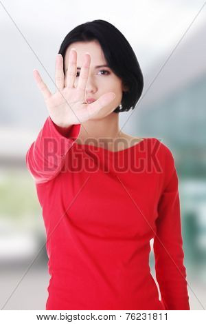 Confident woman making stop gesture sing with hand