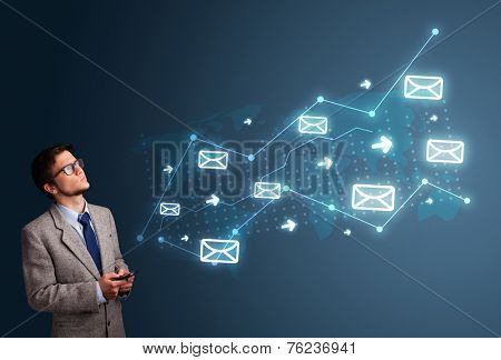 Attractive young man standing and holding a phone with arrows and message icons