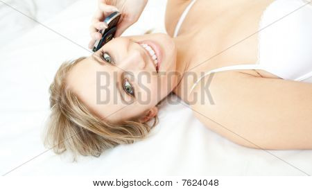 Jolly Woman Talking On Phone Lying On Her Bed