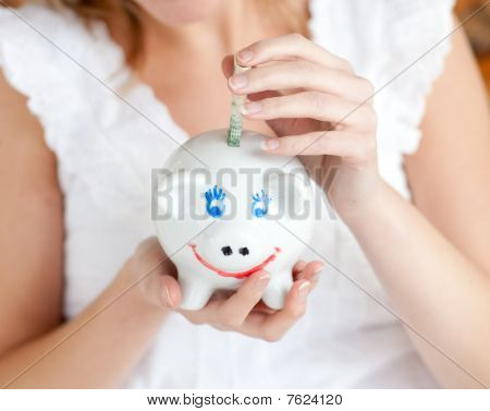 Close-up Of A Woman Saving Money In A Piggy-bank
