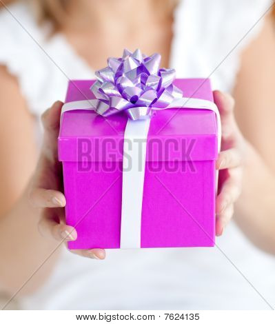 Close-up Of A Woman Holding A Present Sitting On The Floor