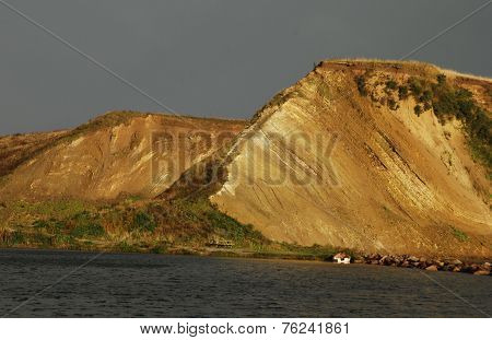 The cliffs stand erect in the morning sun with dark clouds in the background, surrounded by the spar