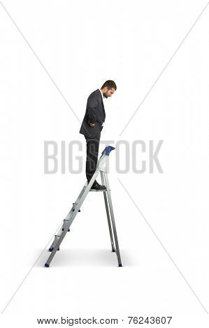businessman standing on the stepladder and looking down. isolated on white background