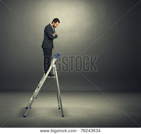 displeased businessman standing on the stepladder and looking down. photo in the dark room