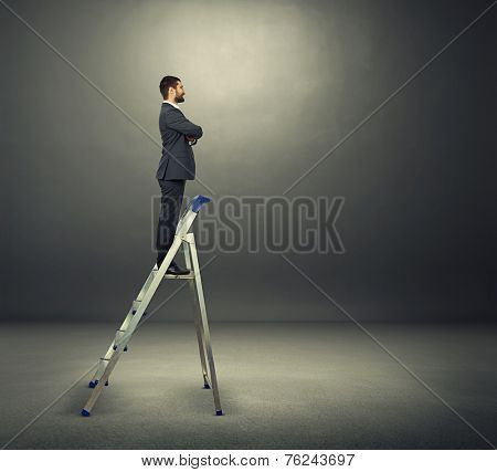 smiley businessman standing on the stepladder and looking forward. photo in the dark room
