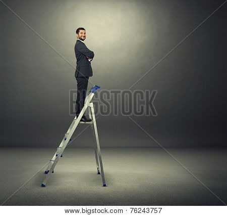 satisfied businessman on the stepladder looking at camera and smiling. photo in the dark room