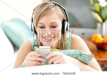 Smiling Blond Woman Listening Music Lying On A Sofa