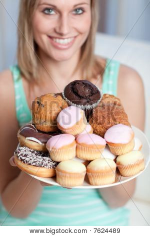 Smiling Woman Holding A Plate Of Cakes