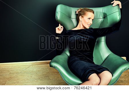 Portrait of a stunning fashionable model sitting in a chair in Art Nouveau style. Business, elegant businesswoman. Interior, furniture.