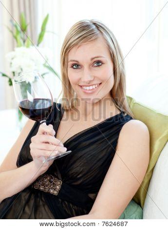 Hermosa mujer desagüe rojo vino sentado en un sofá