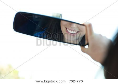 Smiling Woman  Looking In The Rear-view Mirror