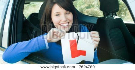 Smiling Teen Girl Sitting In Her Car Tearing A L-sign