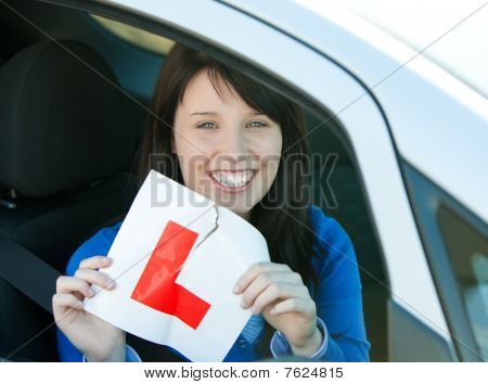Smiling Brunette Teen Girl Sitting In Her Car Tearing A L-sign