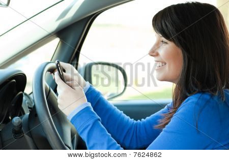 Smiling Teen Girl Using A Mobile Phone While Driving