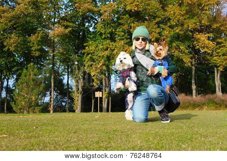 A beautiful girl on the grass smiling with two dogs