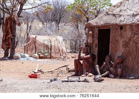 Himba Woman With Childs On The Neck In The Village