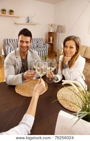 Young couple clinking glasses with friends, sitting at table.