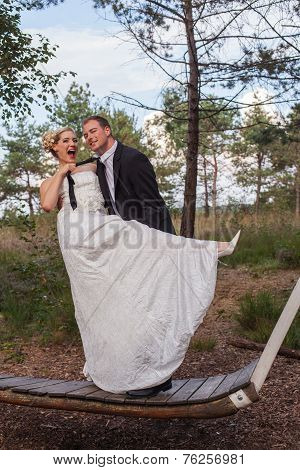 Young married couple is frivolous on a large swing.