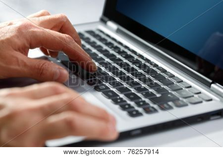 Hands typing on laptop computer