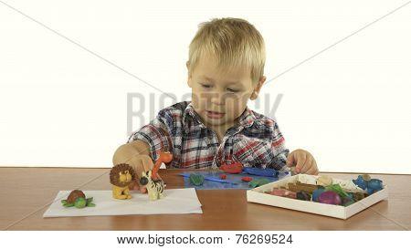 boy sculpts from plasticine animals