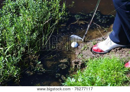 Man chipping ball from water hazard