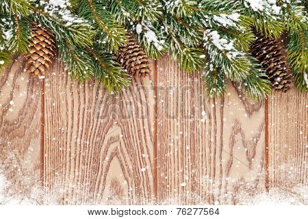 Christmas wooden background with snow fir tree and pinecones