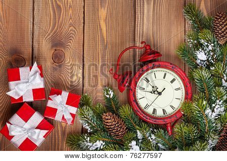 Christmas clock over wooden background with snow fir tree and gift boxes. View from above with copy space