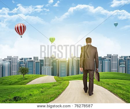 Businessman walks on road. Rear view. City skyline, grass field and sky in background