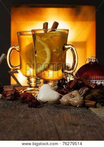Two glasses of tea with christmas decoration at romantic fireplace