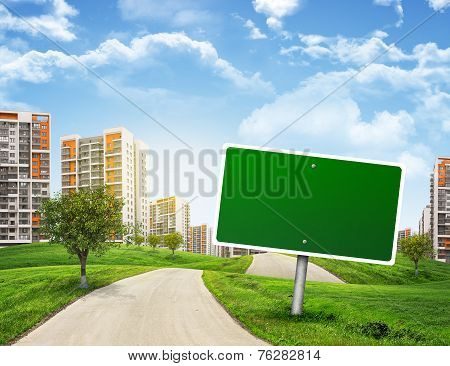 Buildings, green hills and road with empty roadsign against sky
