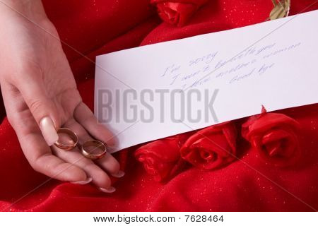 Parting Note. Sad Woman Holding Gold Wedding Ring.